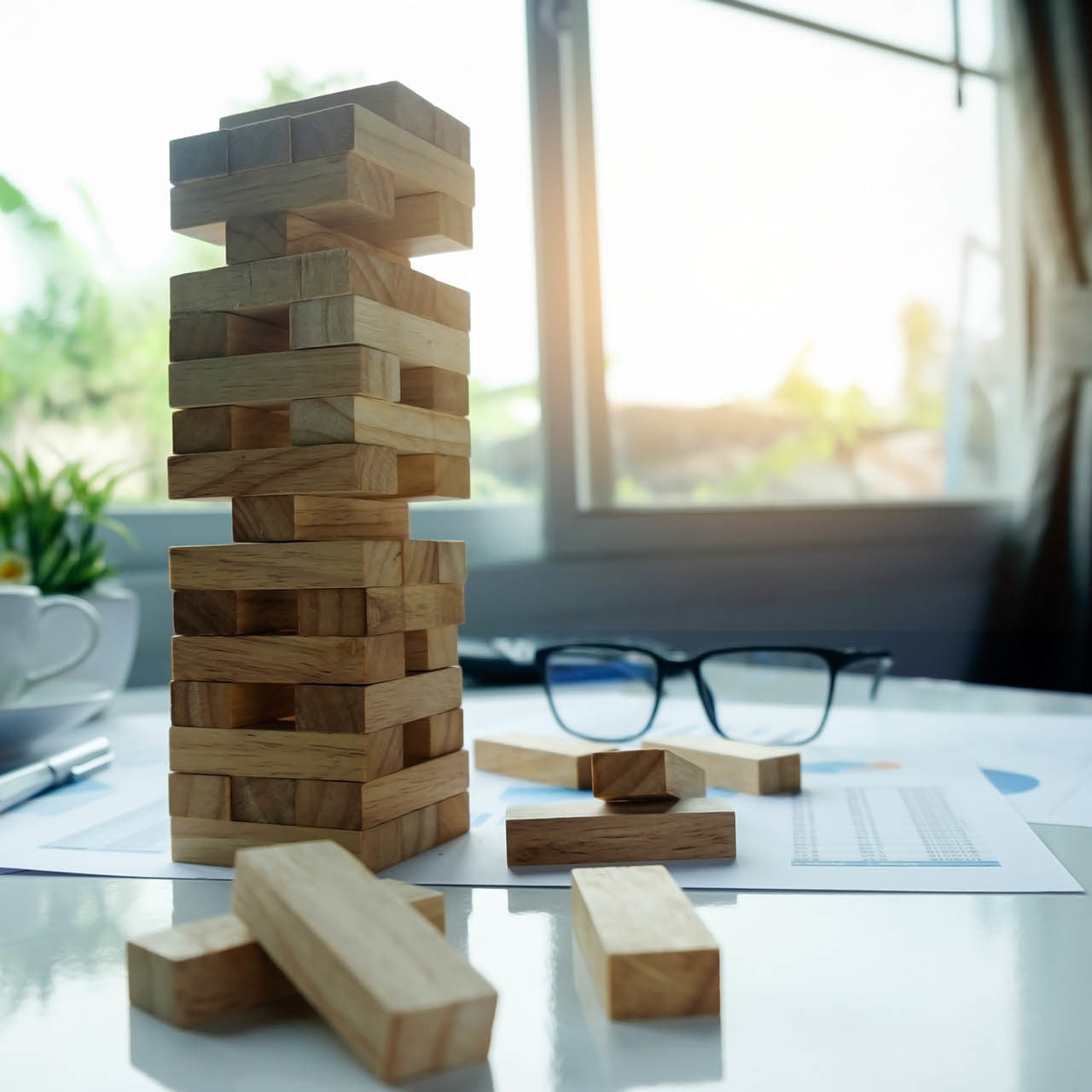 businessman gambling placing wooden block on a tower with meeting background